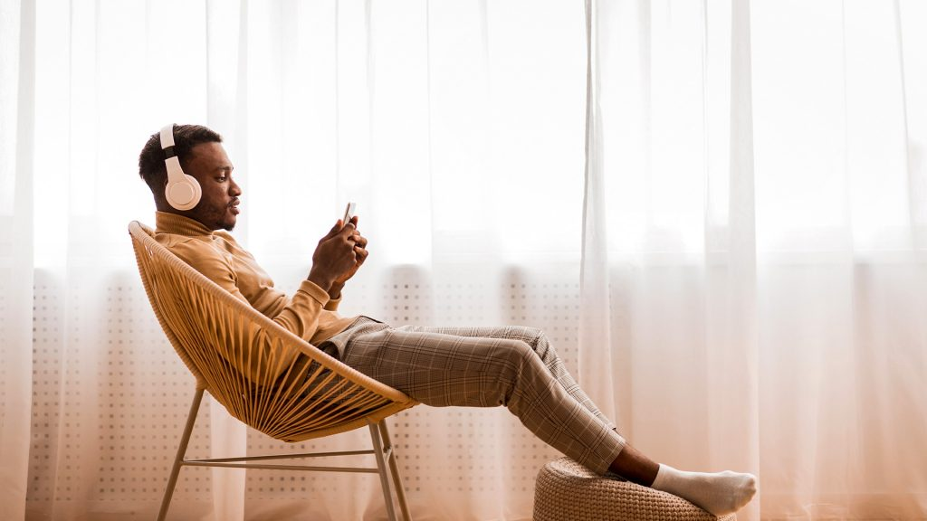 man listening podcast headphones smartphone hero